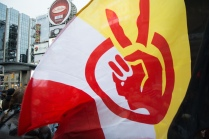 A demonstrator waves a flag during an Idle No More protest on January 11, 2013 in Yonge Dundas Square in Toronto
