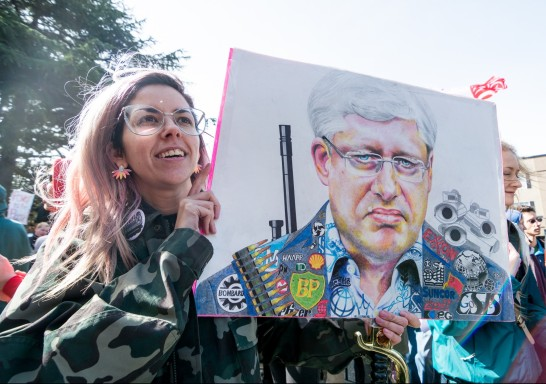 Leah Orton holds an illustration of Stephen Harper at a rally opposing Bill-C51 on March 14, 2015