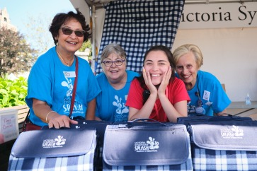 Volunteers (in blue) and VS development coordinator Allegra Bonifacio (in red) pose with Splash picnic blankets at the 30th Victoria Symphony Splash.