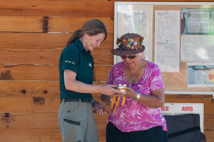 Parks staff passing on a clam rattle gift made by Tsartlip elder May Sam
