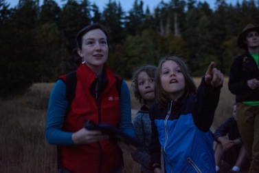 A young participant points out a bat after hearing its call amplified by a bat detector